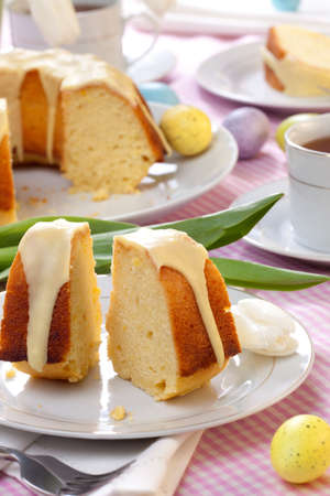 Piece of Lemon Easter cake with lemon icing, served with cup of tea, and decorated with painted eggs photo