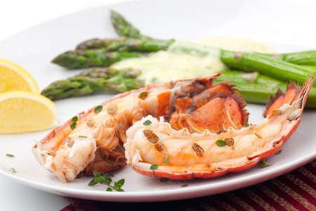 Gros plan des queues de délicieux homard grillé servi avec asperges et sauce béarnaise