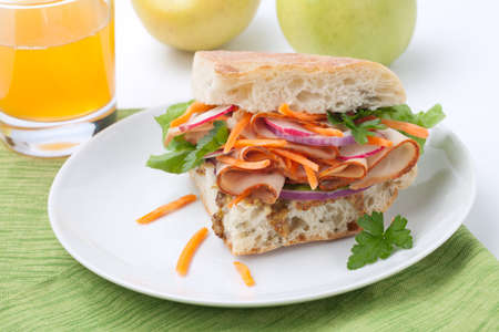 Delicious Turkey Breast Sandwich - rosemary ciabatta bread, turkey breast, whole grain mustard dressing, carrots, radish, red onion and parsley. photo
