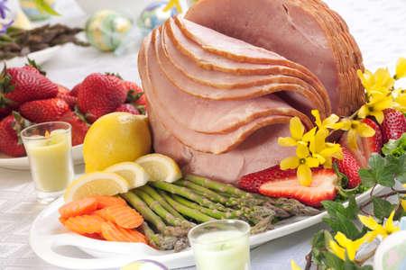 Festive glazed ham for Easter celebration dinner garnished with asparagus, carrots, strawberry, and lemon wedges. Stock Photo