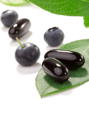 plant drug: Closeup of bilberry extract pills and fresh berries and leaves best suited for alternative medicine ads