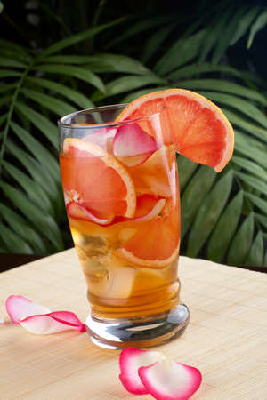 Closeup of glass of grapefruit and rose iced tea on a table in a restaurant on a tropical beach. photo
