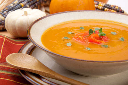 Closeup of a bowl of hot delicious spicy roasted bell pepper pumpkin soup garnished with fresh oregano photo