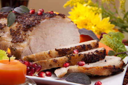 Delicious sliced sage  mustard pork tenderloin with vegetables and pomegranate.