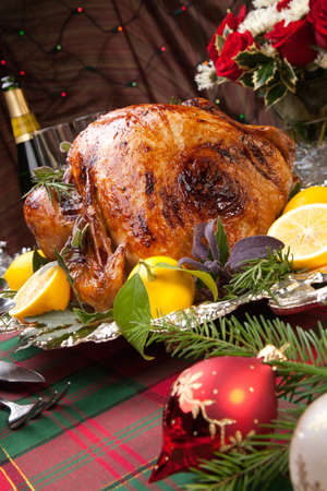 feast: Garnished roast turkey on Christmas-decorated table with candles and flutes of champagne Stock Photo
