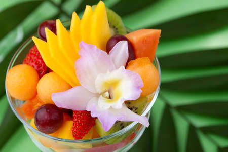 Closeup of serving of fresh tropical fruit salad in cocktail glass. Kiwi, melon, papaya, mango, red grapes, strawberry and orchid flower. photo
