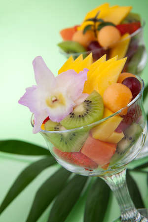papaya flower: Closeup of serving of fresh tropical fruit salad in cocktail glass. Kiwi, melon, papaya, mango, red grapes, strawberry and orchid flower.