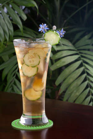 Closeup of glass of ginger and cucumber iced tea garnished with borage flowers on a table in a restaurant on a tropical beach. photo