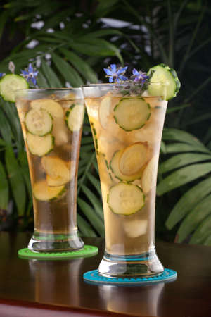 Two glasses of ginger and cucumber iced tea garnished with borage flowers on a table in a restaurant on a tropical beach. photo