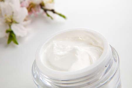 cremas faciales: Detalle de tarro de hidrataci�n crema facial rodeada de flores de almendras Foto de archivo