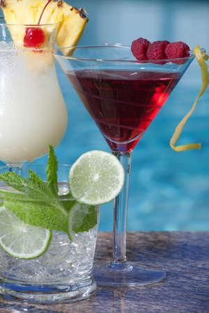 Pina Colada, Mojito and Cosmopolitan cocktails on swimming pool side photo