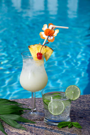 Pina Colada and Mojito cocktails on swimming pool side Stock Photo