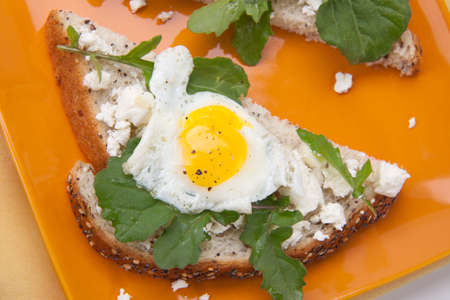 Closeup of delicious open-face sandwiches with feta cheese, arugula, and fried quail eggs. Stock Photo - 9531527