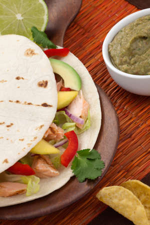 Closeup of grilled salmon fish tacos served with guacamole, fresh tomatoes salsa, and tortilla chips. Stock Photo - 9531510
