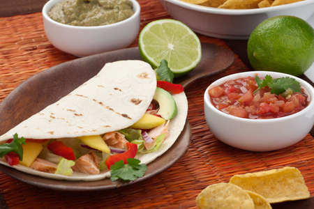 Closeup of grilled salmon fish tacos served with guacamole, fresh tomatoes salsa, and tortilla chips. Zdjęcie Seryjne - 9531534
