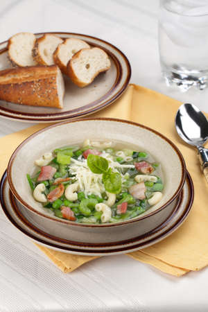 Closeup of bowl of hot fresh Minestrone soup and cheese garlic breadsticks photo