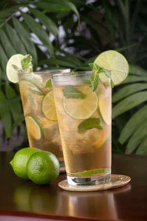 té helado: Dos vasos de Lima y menta Helado té con limón y menta sobre una mesa en un restaurante en una playa tropical.