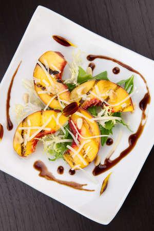 Close-up van gegrilde perziken salade met Parmezaanse kaas en geroosterde pijnboompitten. Balsamico saus. Stockfoto
