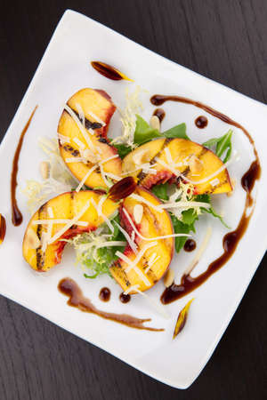 balsamic vinegar: Closeup of grilled peaches salad with Parmesan cheese and roasted pine nuts. Balsamic vinegar sauce.