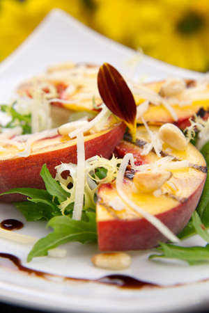 pine nuts: Closeup of grilled peaches salad with Parmesan cheese and roasted pine nuts. Balsamic vinegar sauce.