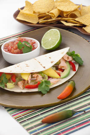 Closeup of grilled salmon fish tacos served with guacamole, fresh tomatoes salsa, and tortilla chips. photo