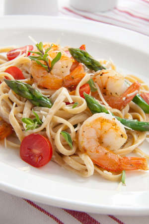 Healthy whole grain linguine with shrimps, asparagus, cherry tomatoes, fresh Parmesan cheese, and  oregano. Stock Photo - 9587324