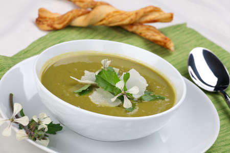 Bowl of pea soup garnished with rocket  arugula leaves and flowers, and shaved Parmesan cheese. Cheese sticks in background. Imagens