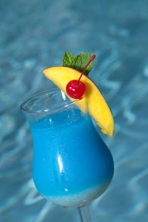 Glass of Blue Hawaiian cocktail on swimming pool side garnished with mango wedge and maraschino cherry