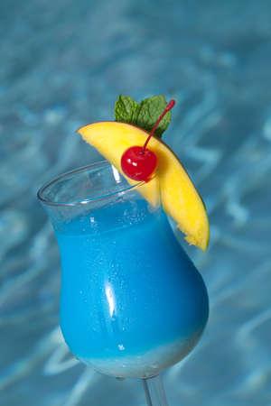 coctel de frutas: Vidrio de Blue Hawaiian cóctel a lado de la piscina con cuña de mango y cereza marrasquino Foto de archivo