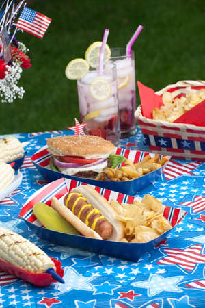 Hot dogs, corn and burgers on 4th of July picnic in patriotic theme photo