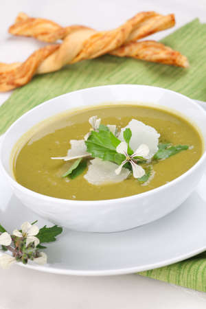 Bowl of pea soup garnished with rocket / arugula leaves and flowers, and shaved Parmesan cheese. Cheese sticks in background. Stock Photo - 9741150