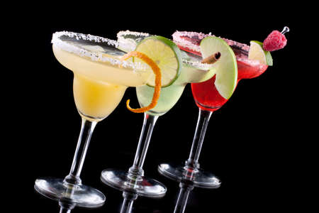 chilled: Three Margaritas - apple, orange and raspberry - in chilled glasses over black background, garnished with slice of green apple, limes, orange twist, raspberry and cinnamon stick. Most popular cocktails series. Stock Photo