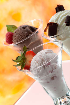 Closeup of delicious vanilla, strawberry, and chocolate ice cream with fresh berries, mint, and chocolate swirls. Stock Photo
