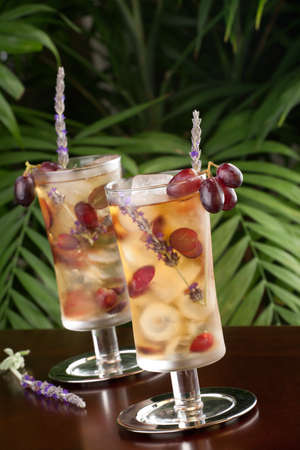 Two glasses of lavender and grapes iced tea garnished with lavender twig on a table in a restaurant on a tropical beach. photo