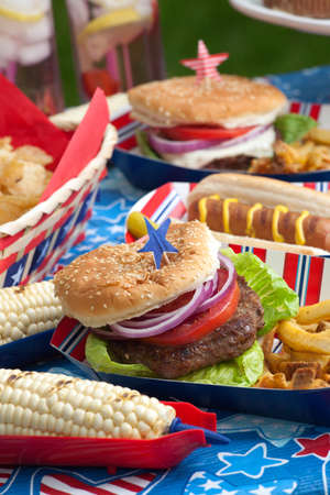 lawn party: Hot dogs, corn and burgers on 4th of July picnic in patriotic theme Stock Photo