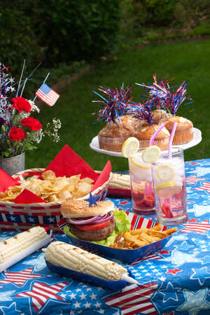 lawn party: Cornbread, corn and burgers on picnic in patriotic theme