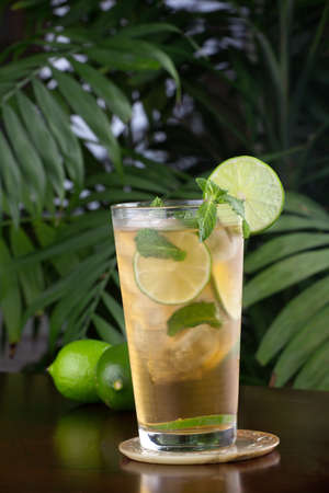 Closeup of glass of lime and mint iced tea garnished with lime and mint on a table in a restaurant on a tropical beach. photo