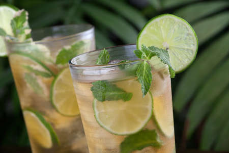 Two glasses of lime and mint iced tea garnished with lime and mint on a table in a restaurant on a tropical beach.
