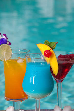 Mai Tai, Blue Hawaiian, and Cosmopolitan cocktails on swimming pool side Stock Photo