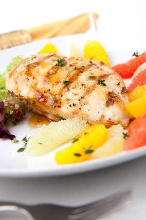 Pechuga de pollo a la plancha con ensalada de cítrico - pomelo rosa, limón, naranja, lechuga y tomillo fresco. Foto de archivo - 9833330