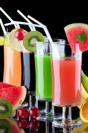 batidos frutas: Vasos de jugos orgánicos de frutas frescas y rodeado por los frescos. Serie sobre bebidas orgánicas y saludables.  Foto de archivo