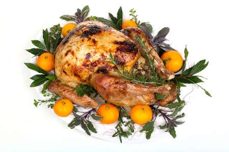 Garnished citrus glazed roasted turkey on tray over white background photo