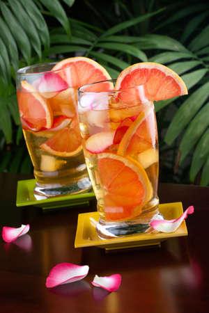 toronja: Dos vasos de pomelo y Rosa t� helado sobre una mesa en un restaurante en una playa tropical.