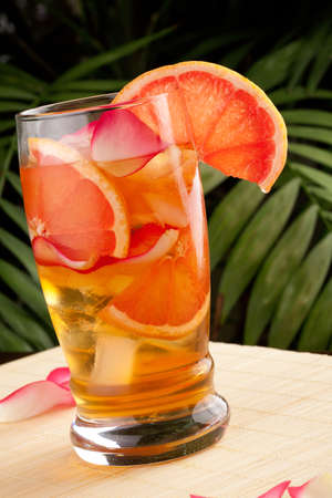 Closeup of glass of grapefruit and rose iced tea on a table in a restaurant on a tropical beach. Stock Photo - 9961406