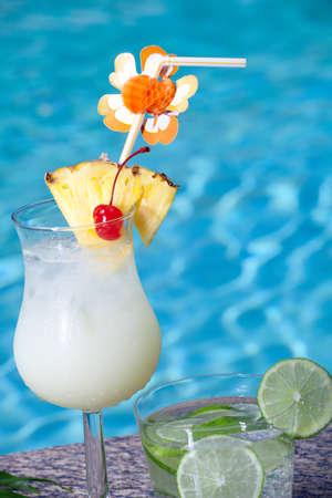 cocteles de frutas: Piña Colada y Mojito cocktails a lado de la piscina
