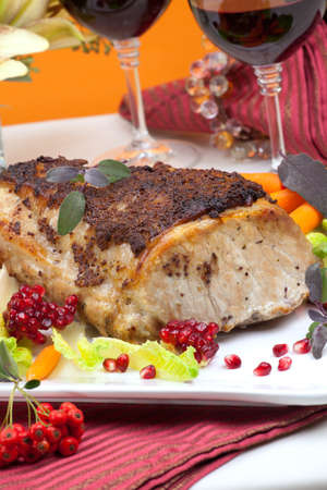 Delicious sliced sage mustard pork tenderloin with vegetables and pomegranate. photo