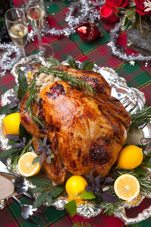 roasted turkey: Garnished roast turkey on Christmas-decorated table with candles and flutes of champagne Stock Photo