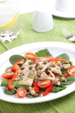 tuna salad with fresh spinach, cherry tomatoes, white beans and pesto dressing. Stock Photo