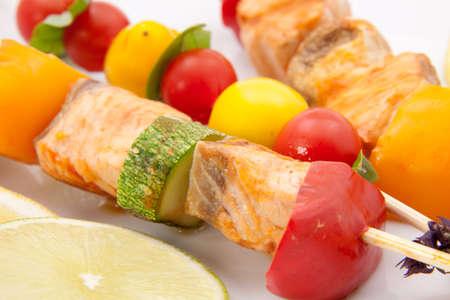 brochetas de frutas: Primer plano de salmón a la parrilla y las brochetas de verduras con estragón fresco y ensalada verde Foto de archivo