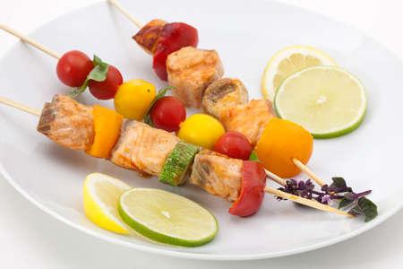 brochetas de frutas: Primer plano de salmón a la parrilla y pinchos vegetales con estragón fresco y ensalada verde